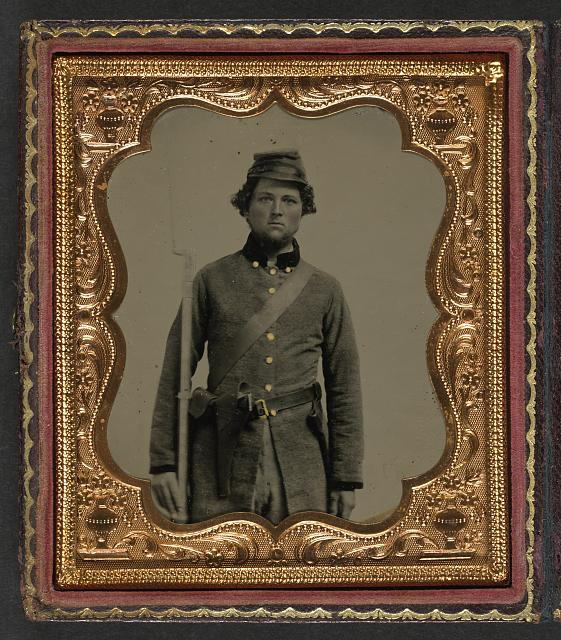 [Unidentified soldier in Confederate frock coat and forage cap with cap box, bayoneted musket, and holstered revolver]