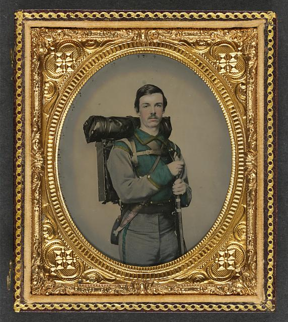 """[Unidentified soldier in Confederate uniform of Company E, """"Lynchburg Rifles,"""" 11th Virginia Infantry Volunteers holding 1841 """"Mississippi"""" rifle, Sheffield-type Bowie knife, canteen, box knapsack, blanket roll, and cartridge box]"""