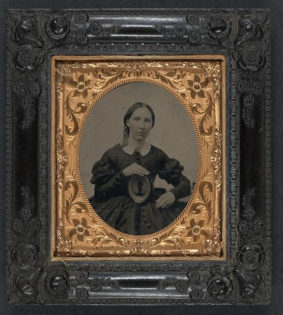 [Unidentified woman wearing mourning brooch and displaying framed image of unidentifed soldier]