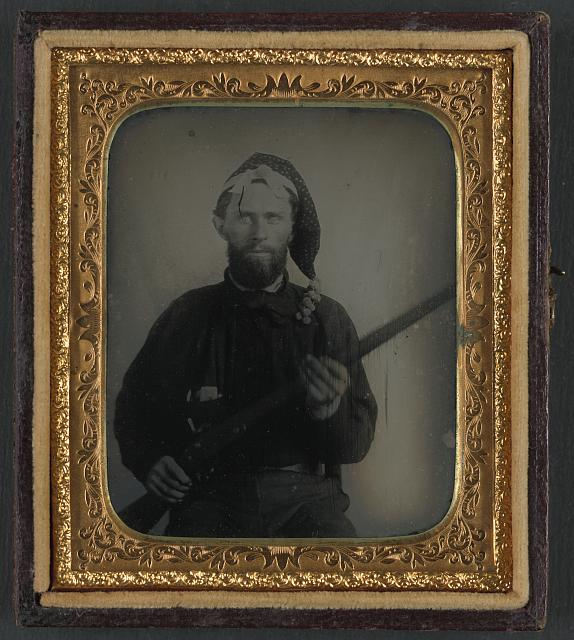 [Unidentified soldier in Confederate uniform and Corsican cap with flintlock conversion musket]