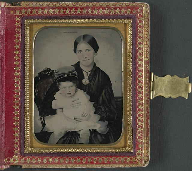 [Unidentified woman, possibly Mrs. James Shields, in mourning dress and brooch showing Confederate soldier and holding young boy wearing kepi]