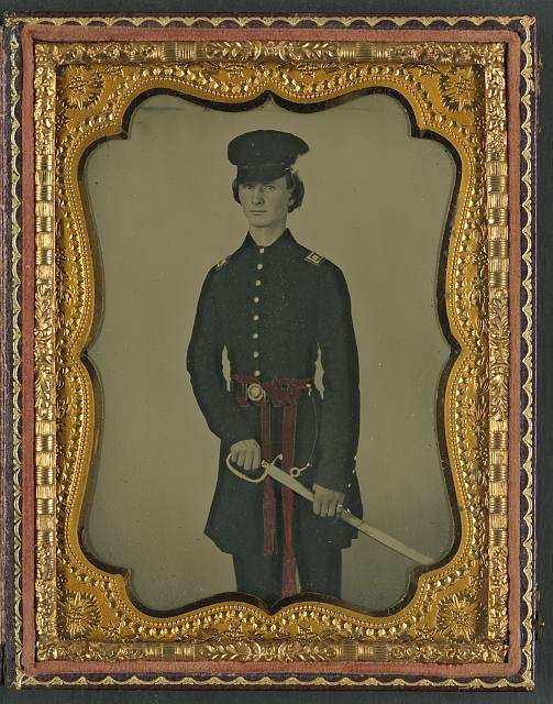 [Unidentified soldier in Confederate uniform and red sash with sword]