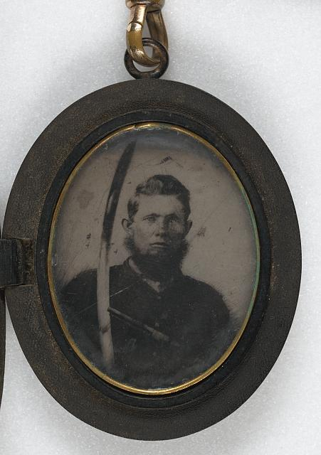 [Unidentified soldier in Union uniform with saber and revolver in locket with chain of braided hair]