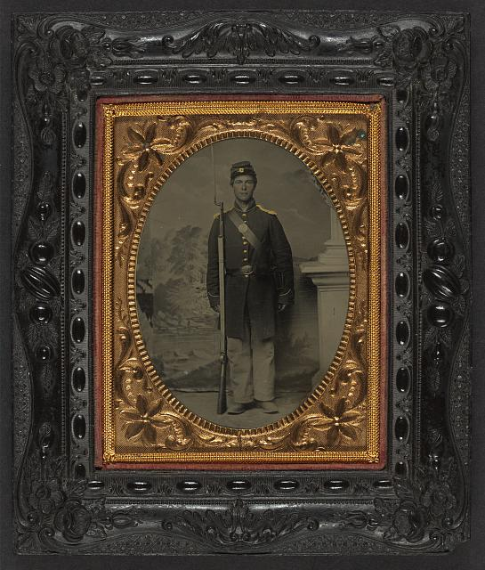 [Unidentified soldier in Union frock coat and shoulder scales with bayoneted musket, cap box, and cartridge box in front of painted backdrop showing lake and trees]