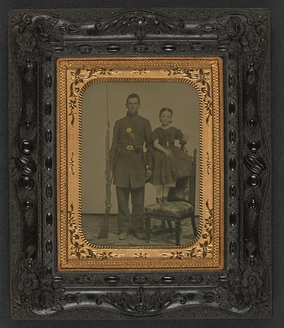 [Unidentified young soldier in Union frock coat with bayoneted musket next to unidentified young girl standing on chair; probably siblings]