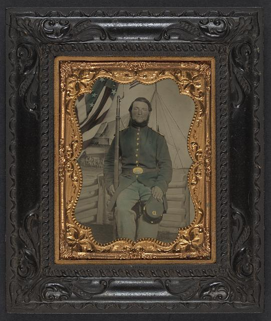 [Unidentified soldier in Union frock coat and shoulder scales with bayoneted musket and Company D forage cap in front of painted backdrop showing military camp]