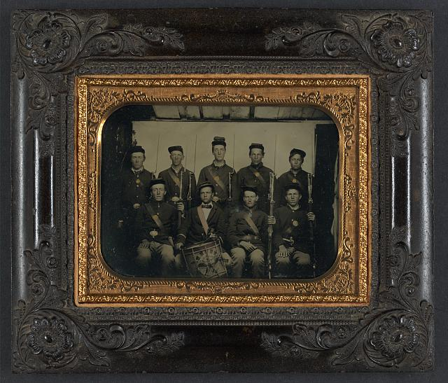 [Nine unidentified soldiers in Union uniforms and forage caps, eight with bayoneted muskets and one with a drum]