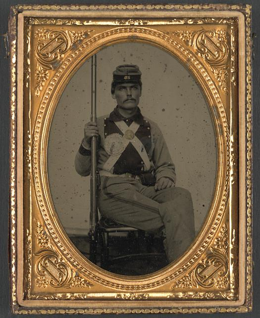 [Corporal John Wesley Edmunds of Co. B, 11th Virginia Infantry Regiment in uniform with secession badge and breastplate holding musket]