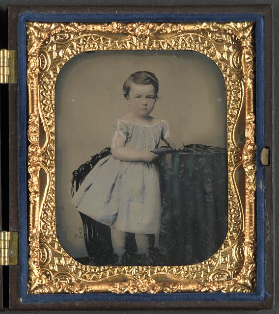 [Unidentified young boy with cased photograph]