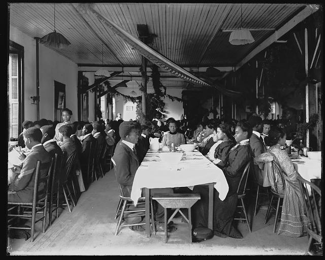[Interior view of dining hall, decorated for the holidays, with students sitting at tables at the Tuskegee Institute]