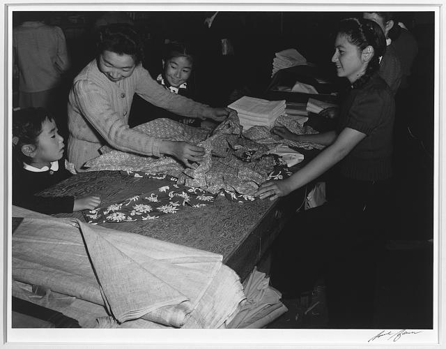 Mrs. Nakamura and family buying clothing, Manzanar Relocation Center