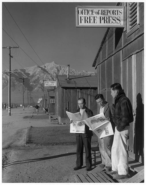 Roy Takeno, editor, and group reading paper in front of office, Manzanar Relocation Center, California