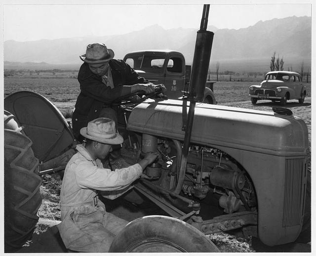 Benji Iguchi and Harry [i.e., Henry] Hanawa, tractor repair, Manzanar Relocation Center, California