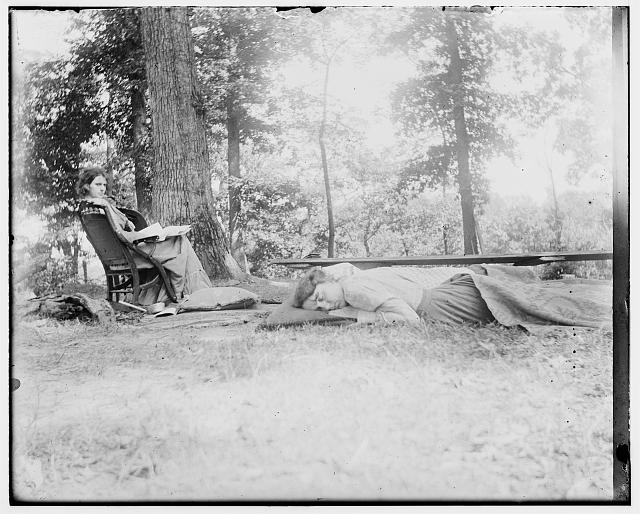 [Katharine Wright lying on the ground, covered by a blanket, her friend Harriet Silliman in a chair nearby, in wooded camp area]