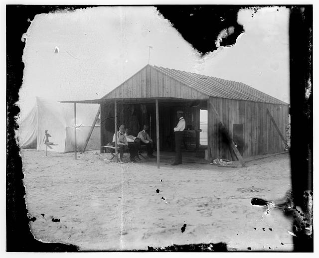 [Visitors and fellow campers in the Wrights' work shed at Kitty Hawk, North Carolina. Left to right: Octave Chanute, Orville Wright, and Edward C. Huffaker seated at left and Wilbur Wright standing]
