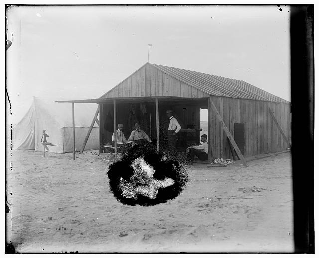 [Wilbur with visitors and fellow campers in front of the Wrights' work shed at Kitty Hawk, North Carolina. Left to right: Edward C. Huffaker and Octave Chanute seated, Wilbur Wright standing, and George Spratt sitting on ground]