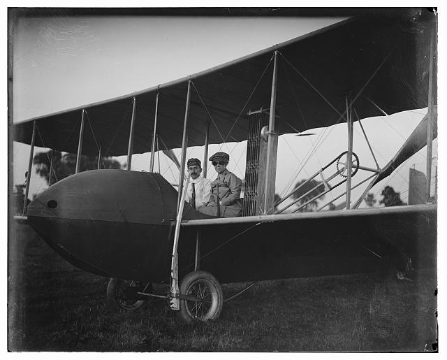 [Katharine Wright, wearing a leather jacket, cap, and goggles, aboard the Wright Model HS airplane with Orville, 1915]