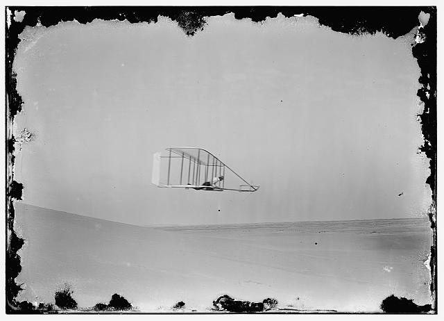 [Side view of Wilbur gliding in level flight, moving to right near bottom of Big Hill; Kitty Hawk, North Carolina]