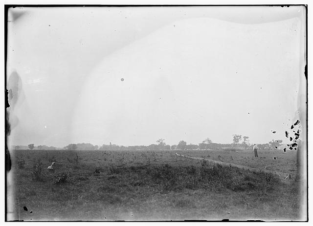 [Damaged machine to the right of the launching track at the end of flight 31, piloted by Orville. The tall, white-shirted man in the foreground may be Charles E. Taylor, Wrights' mechanic; Huffman Prairie, Dayton, Ohio]