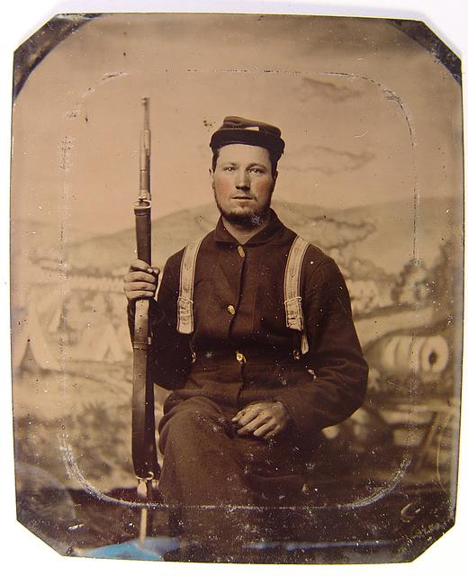[Unidentified soldier in Union uniform with carbine in front of painted backdrop showing military camp scene]