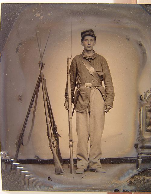[Unidentified young soldier in Union uniform with bayoneted musket next to a rifle stack]