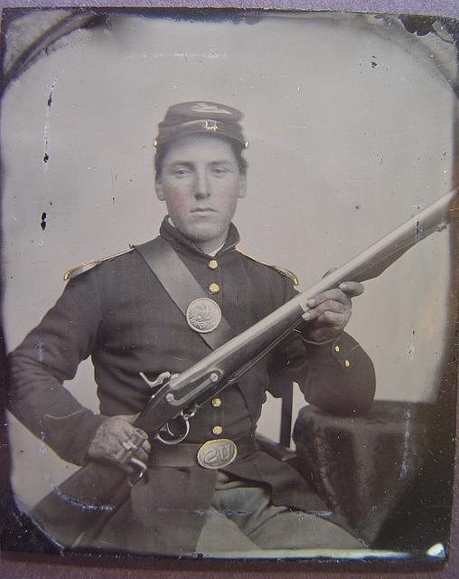[James McGrail in Union uniform with shoulder scales and eagle breast plate sitting with a musket and bayonet in scabbard]