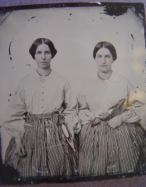 [Sisters Lucretia Electa and Louisa Ellen Crossett in identical skirts, blouses, and jewelry with weaving shuttles]