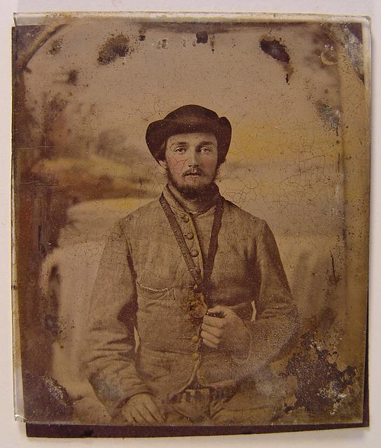 [Unidentified soldier in Confederate shell jacket and slouch hat with object hanging from neck in front of painted backdrop showing waterfall]