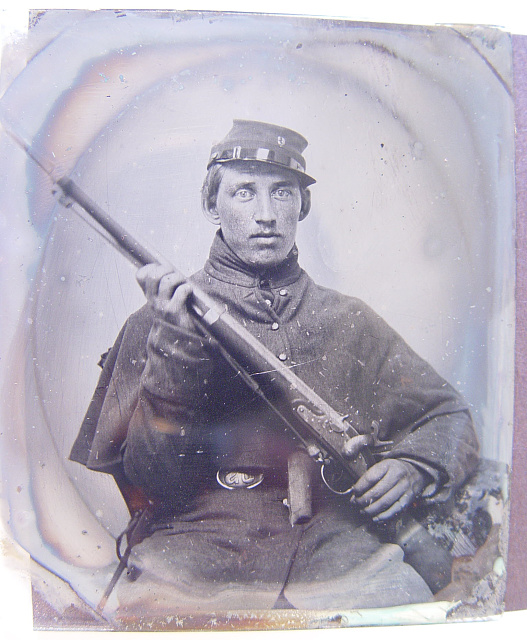 [Unidentified soldier in Union greatcoat and Company C forage cap with musket]