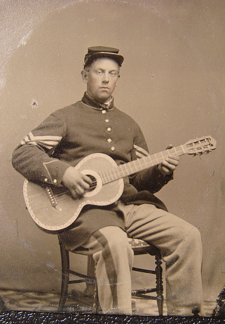 [Edwin Chamberlain of Company G, 11th New Hampshire Infantry Regiment in sergeant's uniform with guitar]