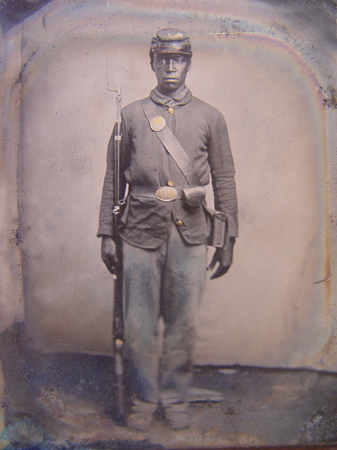 [Unidentified African American soldier in Union uniform with bayoneted musket, cap box, and cartridge box]
