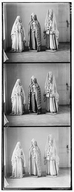 [Three mannequins of women in elaborate dress, on wooden stands]