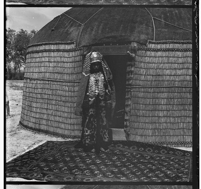 [Woman in traditional dress and jewelry standing on rug in front of yurt]