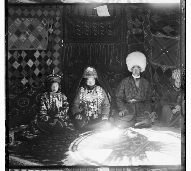 [Four people seated on a carpet, in front of a backdrop of textiles]