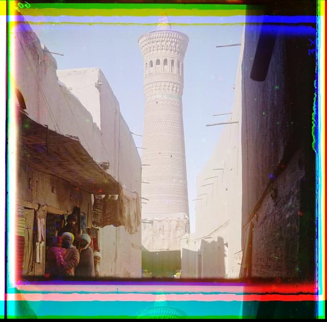 [Street scene with vendors, minaret in background]
