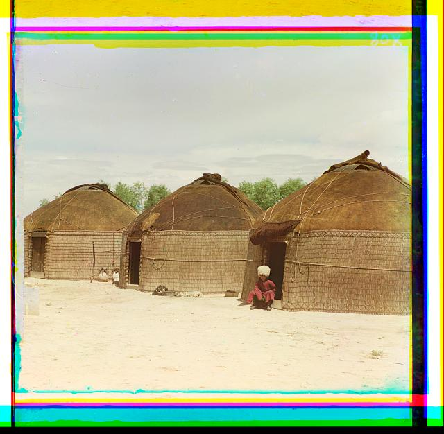[Three yurts, man seated in doorway of yurt in foreground]