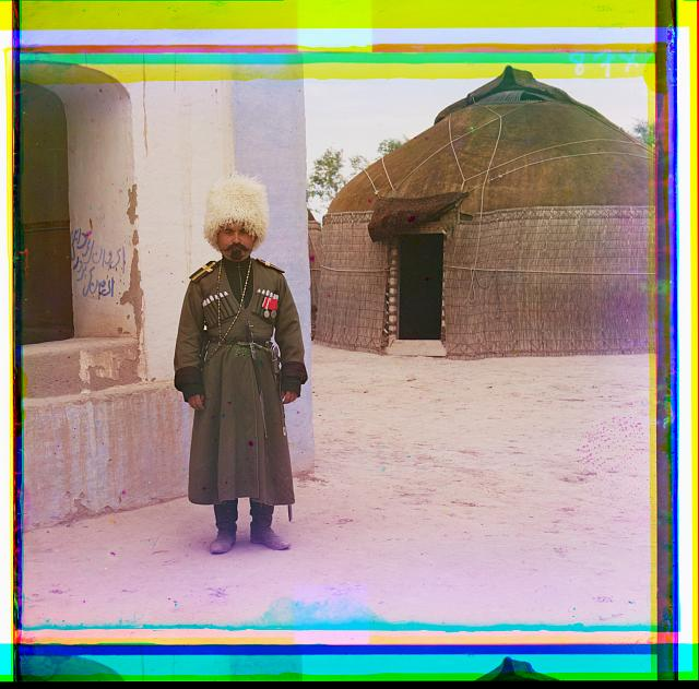 [Man in uniform beside building, yurt in background]