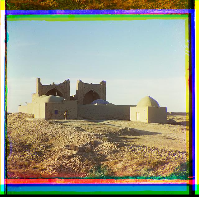 [Walled adobe structure with domes and arches in desert area, with man posed in front]