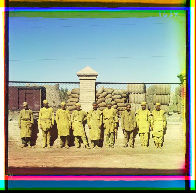 [Group of laborers standing, posed, in front of a chain-link fence, with sacks piled behind fence]