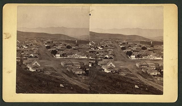 [Unidentified city or town, aerial view, with mountains in the background]