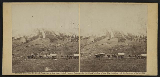 [Three horse-drawn covered wagons in the foreground.  Soldiers marching in formation between rows of small cabins and tents in the background]