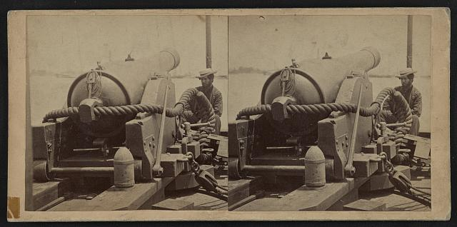 [Rear view of a cannon with a soldier sitting adjacent to it facing forward]