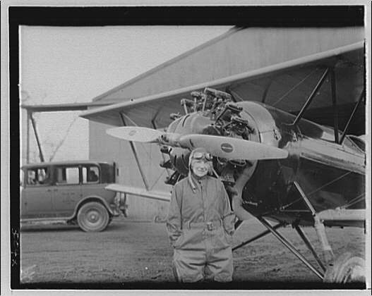 Mrs. Goff at the airport. Mrs. Goff in flying gear in front of airplane