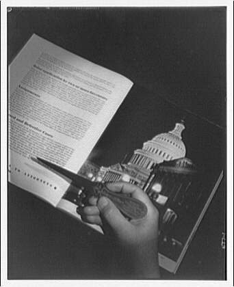 Books. Book open to page of text and photograph of U.S. Capitol with hand and letter opener