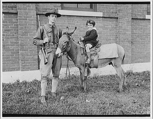 Soldier and child. Man in uniform with child riding donkey