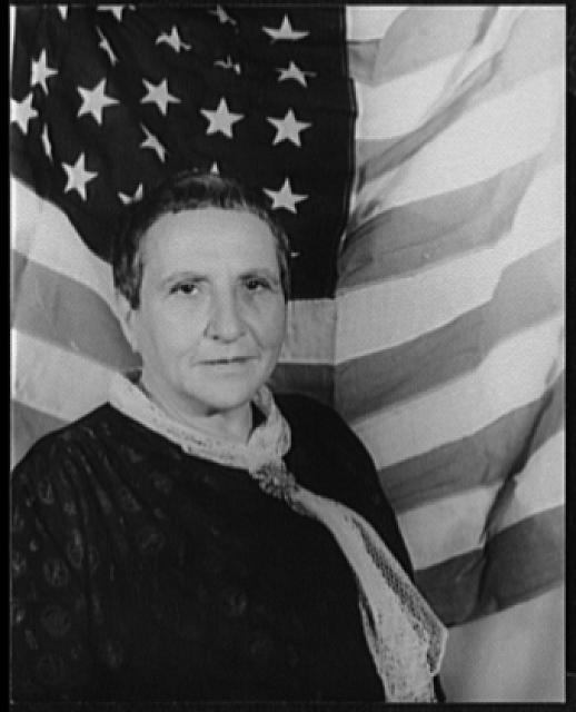 [Portrait of Gertrude Stein, with American flag as backdrop]