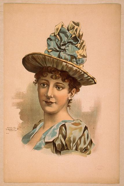 [Head-and-shoulders image of brunette woman, facing right, wearing large blue hat]