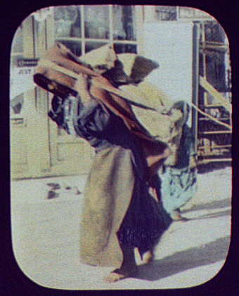 Woman with heavy load strapped to her back