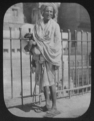 An Indian beggar - standing in front of iron fence
