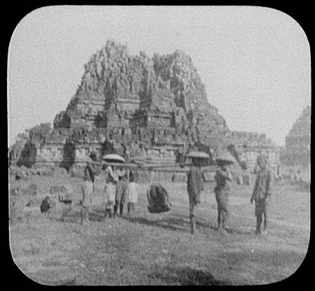 Coolies with sedan chairs in front of ruins of Hindu temple of Prambanan